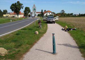 Poller mit dem verletzten Radler am Boden liegend. Dahinter ein Auto eines Helfers. Foto: Radlobby NÖ