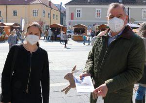 """An Mobilitäts-Stadtrat und Landtags-Abg. DI Franz Dinhobl hat Martina Feirer einen Hasen am Ostermarkt gemeinsam mit dem Flyer """"Frohe Ostern?"""" überreicht."""